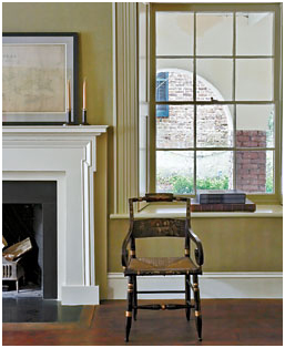 The arcaded lower-level piazza is visible through a window in the library on the ground floor. The mantel is one of the few new architectural elements, the original having been lost. Photography by Paul Costello; Image courtesy G.P. Schafer Architect.