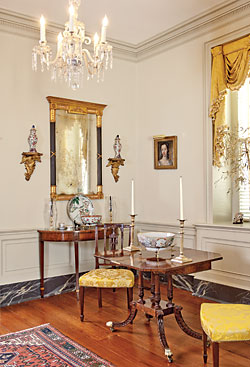 A rare, circa-1800–1810 card table attributed to Charleston is one of the couple's finest pieces. The late John Bivens, a Charleston furniture scholar and private consultant/dealer, felt that, though having elements from other style centers, the details and carving were closely associated with locally made furniture, with decorative elements also relating to Charleston interiors. Conservation of the table revealed that it was made as one of a pair.  The table is flanked by a pair of New York side chairs, circa 1800. A Federal looking glass with ebonized reeded columns hangs above a Federal card table. The portrait of a woman is attributed to John Wollaston (1710–1775); the husband purchased this at an antiques show as a gift for his wife.