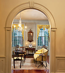 A single door originally gave entry into the drawing room. The couple replaced it with the arch, creating a grander entrance. The circa-1790 sofa is attributed to the New York firm of Slover & Taylor, based on its similarity to a documented example. Directly ahead is a rare, circa-1790 mahogany and satinwood demi-lune card table embellished with lily-of-the-valley inlay, characteristic of the finer shops in Federal-era Charleston. Above the table hangs an elegant Federal looking glass.]