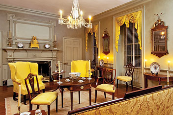 The paneled overmantel and mantel are original to the house and set the tone for this spacious drawing room, which contains elegant examples of Federal furniture. Directly ahead is a circa-1790 Pembroke table with bookend inlay, probably from New York. The square-back chair to the right, is a rare inlaid circa-1800 New York example, detailed with bellflowers, carved plumes above, and a carved sunburst at the base. See caption on facing page for details of the demi-lune card table and looking glass to the right of the window. The circa-1790 New York demi-lune, five-legged card table to the left of the window features bookend inlay similar to that on the Pembroke table.