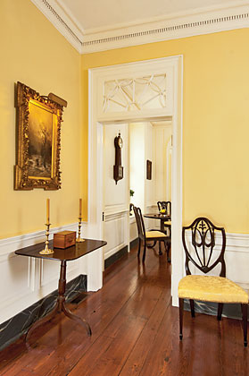 Light shines in from the side garden door and the kitchen window to the left of the breakfast room. Though she originally wanted to live on a more secluded street, the wife now enjoys the bustle of tourists passing her house as she drinks coffee with her husband at the circa-1760 Philadelphia tilt-top table; the chairs are of the same period and time frame. A Federal tilt-top table, over which hangs a French landscape, and New York chair, one of a pair, are in the entry.