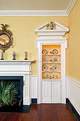 The couple added the broken-arch pediments in the dining room as well as the recessed cabinets on either side of the fireplace mantel, which is original to the house. The pre-1790 armorial Chinese export porcelain was acquired from Elizabeth Sharpe, John Suval, Polly Latham, and the late Elinor Gordon.
