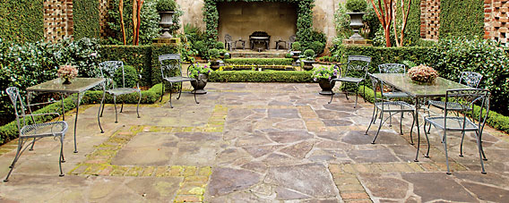 "The walled garden behind the house was once the location of a brick warehouse; its back and side exterior walls now form the garden perimeter. The courtyard is seen as an extension of the house and is divided into vignettes set at different elevations, with a koi pond and canopied vestibule toward the rear, and trimmed creeping fig outlining the original warehouse window surrounds. The use of outside ""rooms"" was a hallmark of landscape architect Loutrel Briggs (1893–1977), who designed this garden and numerous others in Charleston. The garden is illustrated in James R. Cothran's Charleston Gardens and the Landscape Legacy of Loutrel Briggs (2010)."