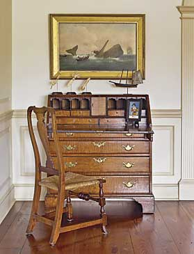 The figured maple Chippendale slant-front desk was one of the couple's early purchases. The German églomisé painted scene is a rendering of Autumn, circa 1830. A Spanish-foot Queen Anne maple side chair is pulled up to the desk. The couple purchased the painting of the whaling scene from Fred Giampietro at the Winter Antiques Show in 1988. This picture reminds the couple of Nantucket, where they have a home, and ties in with the island's history of whaling. The miniature ship weathervane, from Olde Hope, was possibly used on an out building such as a shed. Continuing the nautical theme are three scrimshaw pie crimpers, purchased from Hyland Granby Antiques.