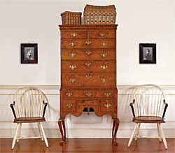 "The owners wanted a Queen Anne high chest, and Olde Hope located this one in a private collection. Made of figured maple, it is from Rhode Island, circa 1740–1760, and is of an unusually small size with pleasingly narrow proportions. Flanking the high chest is a pair of circa-1800 Philadelphia bow-back Windsor chairs with original white paint, mahogany arms, leather seats, and branded ""Cox"" (from Northeast Auction's Arthur Spector, 2004). Above the chairs is a fine pair of profile portraits in original frames of Mr. and Mrs. George Buckingham, Pennsylvania, circa 1830, attributed to Mr. Boyd. Surmounting the high chest are Native American Woodlands tribes baskets with original ""swabbed"" decoration."