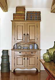 "The New Jersey step-back cupboard with dramatic scalloping retains its original tan paint. ""I think the wear pattern is as interesting as the paint,"" says Patrick Bell. ""It becomes a design element."" Woodlands baskets provide color on top of the cupboard, as does the graduated stack of firkins with original blue paint. Displayed on the cupboard is a portion of the wife's extensive collection of blue-decorated spongeware. The nineteenth-century New England sawbuck table retains its original red paint and scrubbed top."