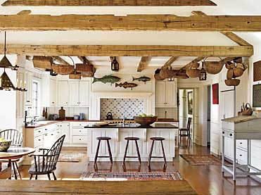 When home, the couple spends most of their time relaxing, cooking, and enjoying family in the kitchen. Patrick Bell and David Guilmet of Bell-Guilmet worked with the owners to personalize the space. Because of its open plan, they warmed the space by using reclaimed hand-hewn beams to bring the eye down from the high ceilings. Part of the wife's collection of antique candle lanterns and oak and ash splint baskets also provide visual depth. The cod weathervane on the left was one of the couple's early purchases from Olde Hope Antiques; they purchased the other fish weathervanes from the firm as well. On the center island is a large treenware bowl and wooden cutting boards. Visible along the right wall is some of their game board collection, acquired for their checkerboard patterns and simple graphics and colors. The early nineteenth-century stretcher-base schoolmaster's desk retains its original grey paint. Visible in the dining room beyond is a Hudson Valley naïve landscape. In front of the window on the left is a large oval maple hutch table from New York state; its original red wash remains on the base. The Windsor chairs and stools are reproductions. The early nineteenth-century chandelier is from the Lammot du Pont Copeland collection.
