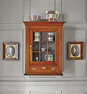 "The Pennsylvania Chippendale cherrywood hanging wall cabinet, circa 1790, was purchased at Sotheby's in 2002 from the Gunston Hall Plantation collection. Within and on top of the cabinet is part of the couple's collection of mocha ware. One of a pair of portraits by ""Mr. Boyd"" flank the cabinet."