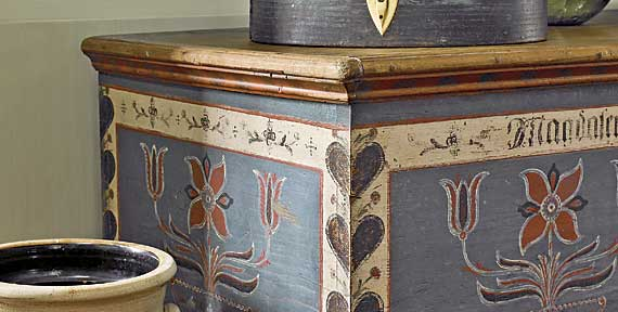 "The blue-painted carrier and Pennsylvania dower chest from the previous image are shown with a cobalt-decorated New York stoneware churn stamped ""Maker-M. Woodruff, Cortland."""
