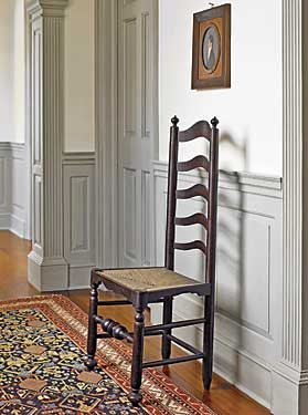 "One of two similar ladder-back side chairs with original surface lining the hallway. With its applied skirts, dramatic bulbous turned stretcher, and suppressed ball feet, this chair exhibits a classic Delaware Valley form. Above the chair is one of several profile portraits in the collection, with their classic grey background, dating between the 1810s to 1840s, and attributed to ""Mr. Boyd,"" of central Pennsylvania. Though his identity is not confirmed, it is possible Mr. Boyd was a portrait and furniture painter working in the Harrisburg area."