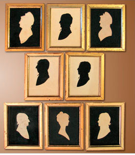 "Fig. 1: William Jennys (1774–1859), family group of eight silhouettes, ca. 1805. White paper mounted on black cloth, the hollow-cut silhouettes each 4-3/4 x 3-3/4 inches and the ""hole in the doughnut"" inside silhouettes each about 3 x 2-1/2 inches. The three hollow-cut examples are embossed ""W. Jennys.""  Private collection.  Using both methods of silhouette cutting, Jennys produced an unusual alternating pattern of white and black images within this family group."