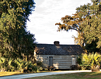 Fig. 15: HCF's easement protects the acreage and outbuildings around the main residence at Mulberry Plantation, including this restored slave cabin. The cabin, of wood-frame construction, would have housed two families. The pond behind the cabin is a former impoundment used for rice cultivation. Photography by Rick McKee.