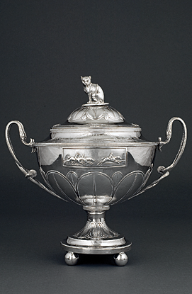 "Horse Racing Trophy, William Fountain, London, England, ca. 1803. Inscribed ""Roxana Winning a / Jockey Club Purse / at Washington Course / in Charlestown [sic], South Carolina /  Feby [sic], 1802"" and bearing the McPherson crest and arms. Silver. H. 16-1/2, L. 15-1/2 in. Courtesy, the Rivers Collection, Charleston, S.C. Photograph provided by the Gibbes Museum of Art. 