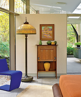 The Tiffany floor lamp, with its curtain glass border and pigtail finial, glows at night and echoes the yellow-green hostas in the garden in the daytime. The Gustav Stickley desk designed by the architect Harvey Ellis provides a place for a select collection of sculptural Grueby pottery with its leathery glaze. The painting is by plein air artist Henry Ryan MacGinnis (1875–1962). The contemporary purple Phillips chair by Rodolfi Dordoni for Minotti was made in Italy. The adjoining bathroom, with its pod-shaped shower, which Dennis designed with his uncle, sculptor Harold Kimmelman, has views of the secluded garden. For privacy, there are pocket doors, electrically operated shades, and a glass panel from the top of the wall to the ceiling.