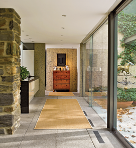 To unify the interior and exterior spaces, Dennis used masonry paving matrix for the floors of the terrace and throughout the house; the exterior and interior walls are all reinforced concrete. The blending of contemporary materials and period furnishings is seen at the end of the hallway where, placed against a concrete wall, a Connecticut tiger-maple chest of drawers, becomes a pedestal for a collection of pewter.