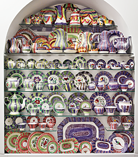 "Displayed on recessed glass shelves, rainbow spatterware creates a symphony of color in the main first floor entry; each piece plays its part in orchestrating color cords. Dennis first discovered spatterware at Pennypacker's auctions near Reading, Pennsylvania, when he was a teenager collecting Historical Blue Staffordshire. ""A friend of my mother's collected spatter and I would buy some for her at auctions, and when she didn't want what I bought, I kept it,"" he said. His collection, which fills three alcoves, is exclusively rainbow spatter, four- and five-color stripes, festoons, pinwheel, and bull's eye patterns on full and child size tableware. This collection is complete; when something comes in something must go out."