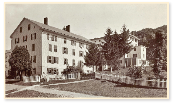 "View of large Shaker buildings with a brother standing in front, from ""Views of North Family Shakers at Mt. Lebanon, New York,"" by J. E. West., No. 25 of the series, First and Second Houses."
